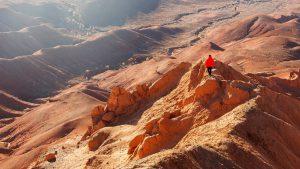 Турист в красном на вершине горы