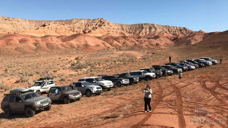 Туристка из числа джиперов на фоне гор и внедорожников