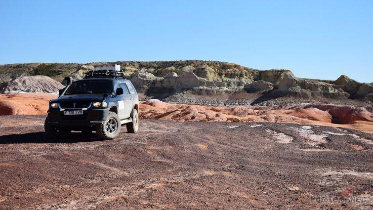 Внедорожник на фоне пёстроцветных глинистых скал