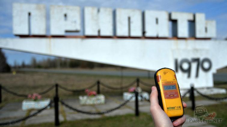 Рука с дозиметром на фоне стелы города Припять
