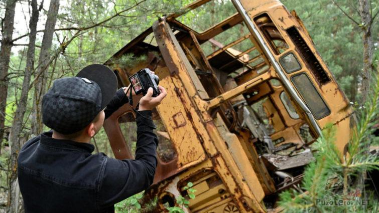 Турист фотографирует ржавый автобус в лесу