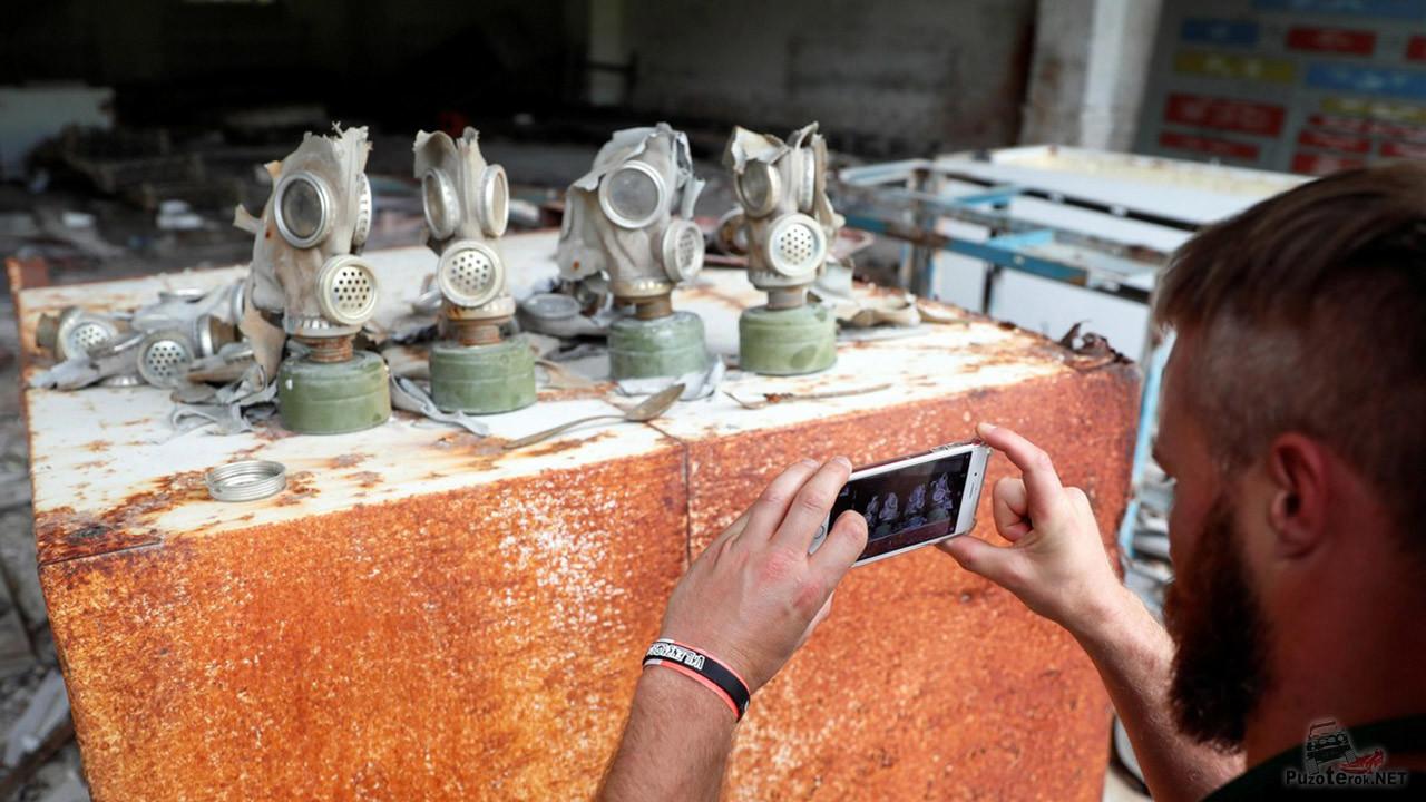 Турист-сталкер фотографирует ряд противогазов