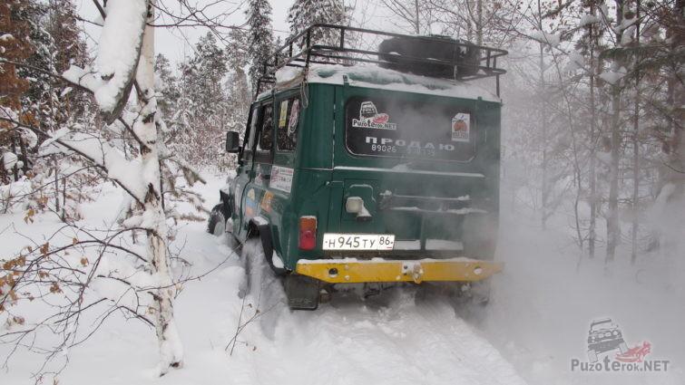 Зелёный уазик едет по глубокому снегу