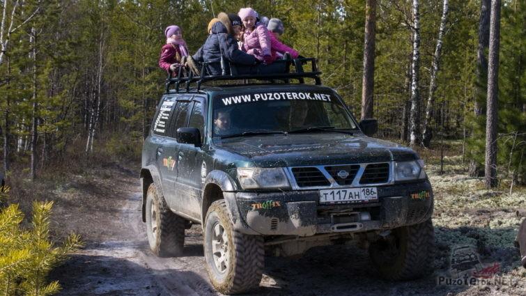 Дети катаются на багажнике внедорожника