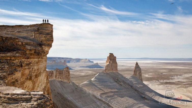 Туристы на вершине скалы над пустыней