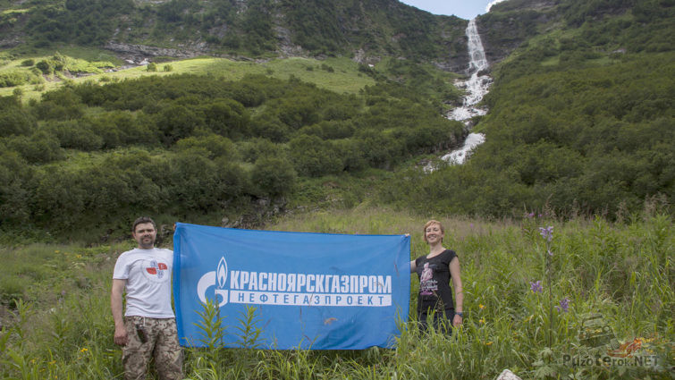 Туристы с корпоративным флагом на фоне водопада