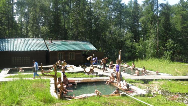 Туристы в летних термальных источниках
