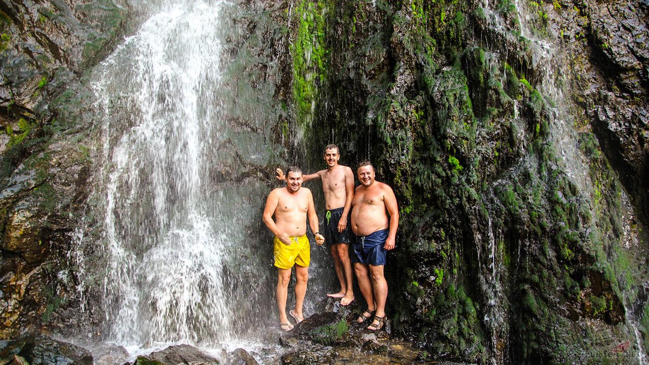 Туристы под холодными струями водопада