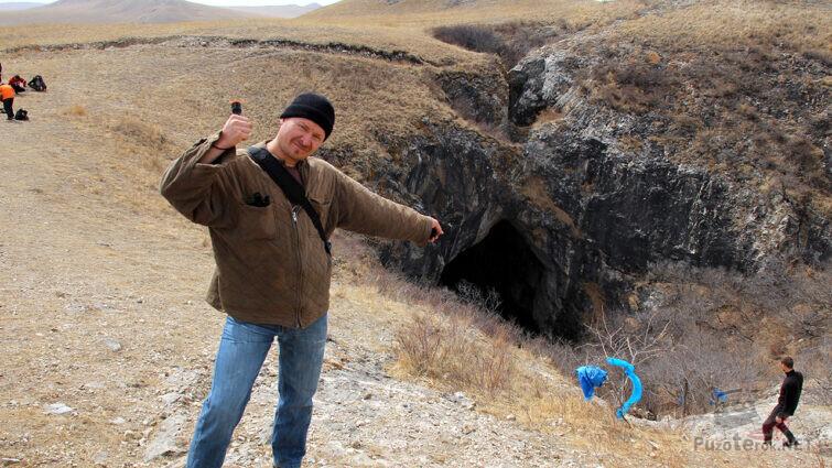 Турист рядом с дырой в степи
