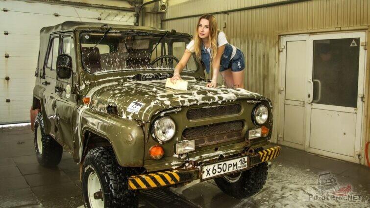 Девушка стоя на колесе моет уаз-469