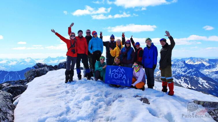 Группа туристов с флагом своего клуба на вершине Народной