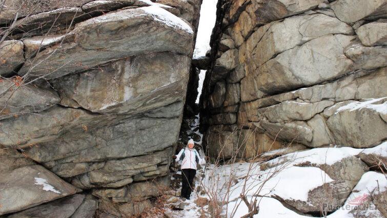 Крошечная фигура туристки у основания скальных останцев