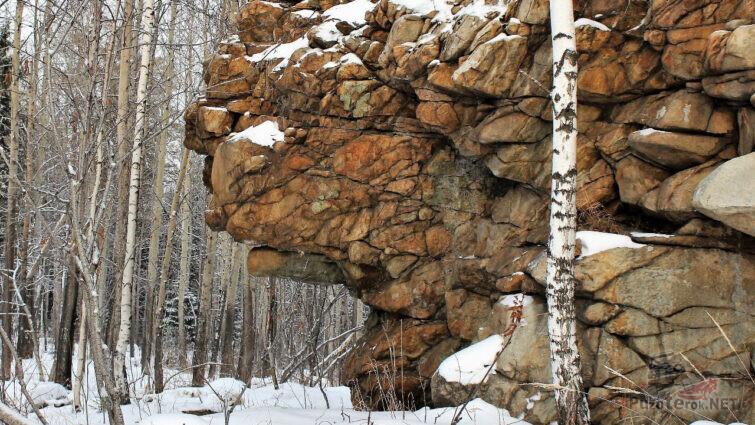 Скала Миротворец среди зимнего леса на вершине горы