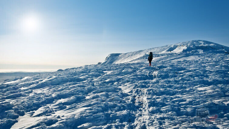 Турист идёт среди сугробов к вершине горы