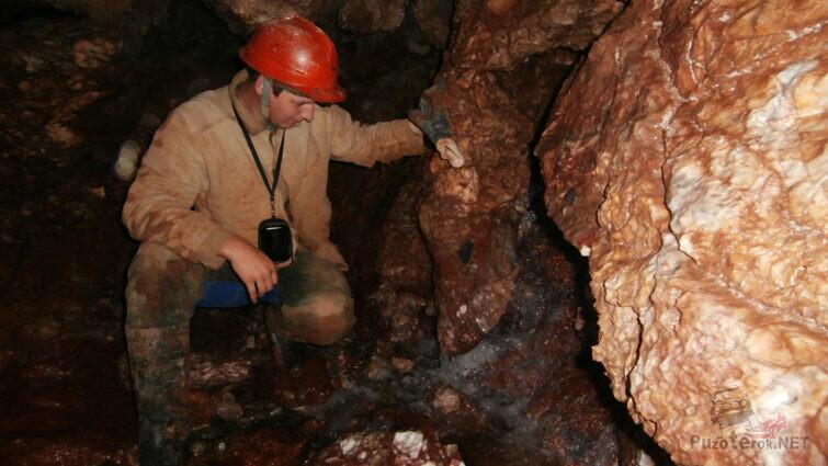 Турист на берегу реки Лысан внутри пещеры