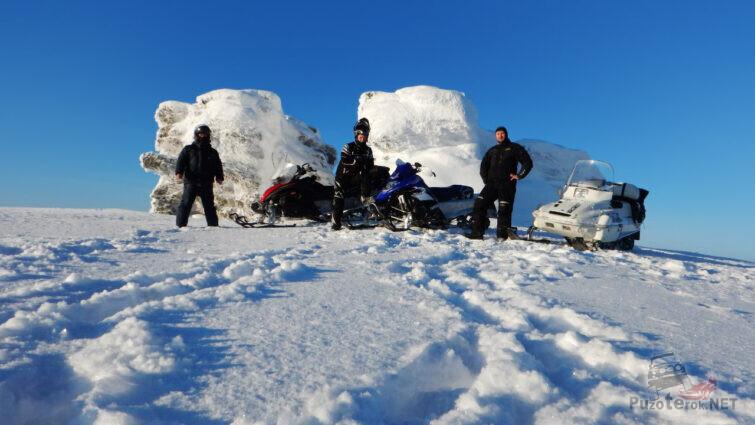 Туристы на снегоходах у заснеженных скал Три брата