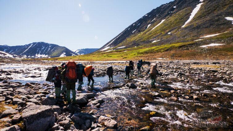 Туристы переходят брод на пути к вершине горы
