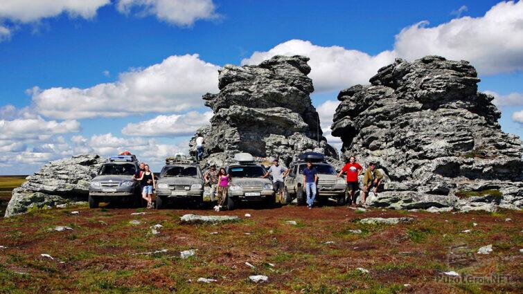 Туристы рядом с внедорожниками у скал Три брата