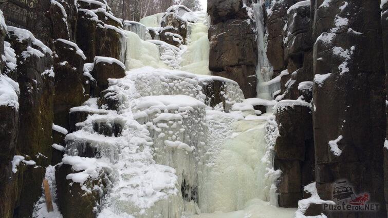 Застывший и заснеженный зимний водопад